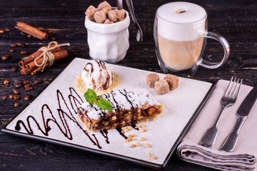 Apple strudel with ice cream ball, served with cinnamon coffee