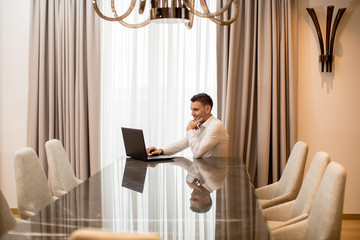 Young man sitting in a luxurious room in front of a laptop computer
