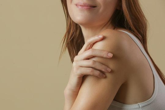 Woman applying body cream on arm, beauty skin care concept, studio shot