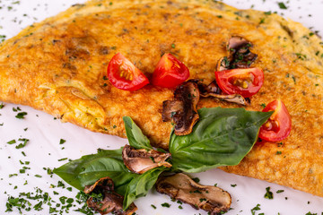 Egg omelet, served with fried mushrooms and cherry tomatoes