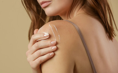 Woman applying body cream on arm, beauty skin care concept, studio shot