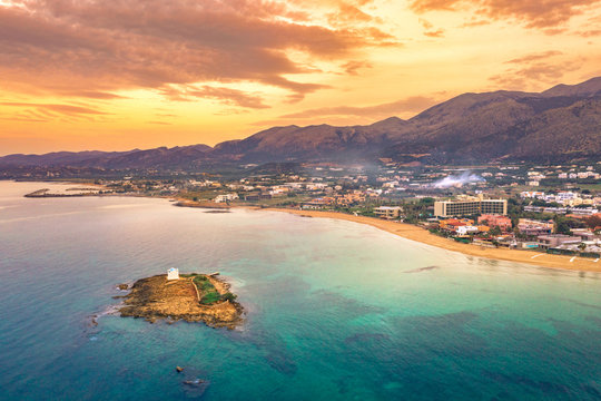 An old white church in a small island at sunset in Malia, Crete, Greece.