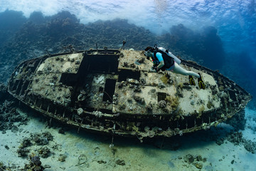 woman diver visiting an underwater wreck of a metal sailboat on a reef in the Rea Sea, Egypt