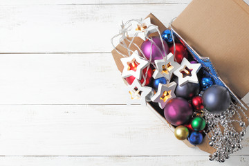 Fototapeta Box with Christmas or New Years toys on a white background, place for text, flat lay.