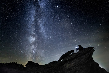 Photographer night sky in mountains with camera in tripod