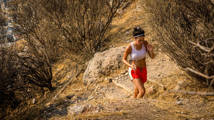 Teen in red shorts running on trail on mountain