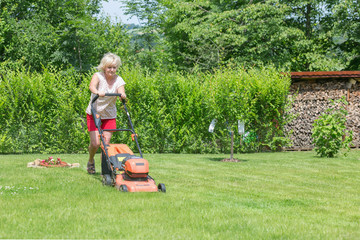 Woman mows the grass in the garden