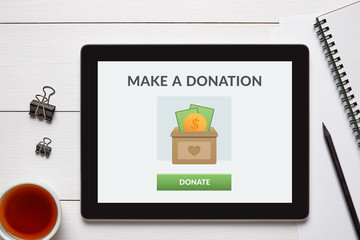 Donate concept on tablet screen with office objects on white wooden table. Top view