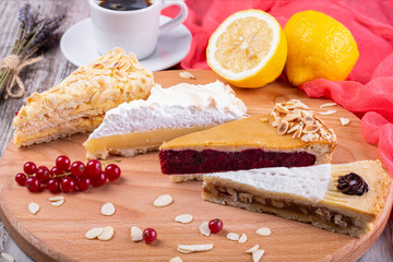 Caramel, nut, cherry and lemon cakes with decor on wooden board