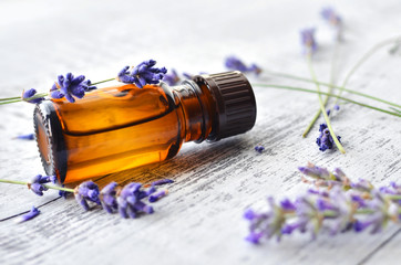Organic herbal oil in dark glass transparent bottle and fresh lavender flowers on old wooden background. Aromatherapy treatment.