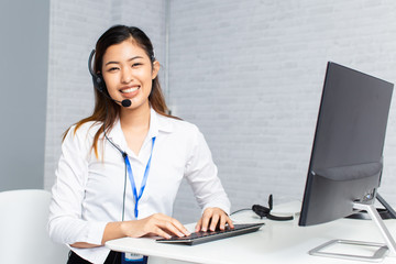 Happy Asian woman with headset smiling and looking at camera while using computer during work in office of call center