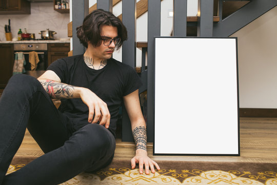 Man holding a picture frame or poster for mock up wearing black clothes in a room interior