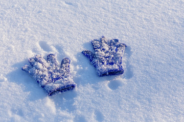 Two kids blue mittens with adhering snow lying down on snow
