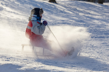 Keuken foto achterwand Wintersporten happy boy riding at the slide on snowy hill