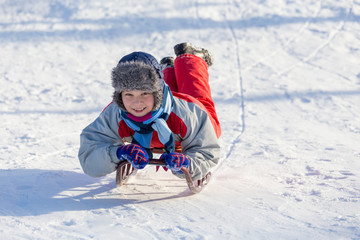 happy boy riding at the sledge on snowy hill