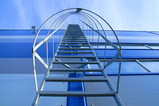 A metal staircase on the facade of an industrial blue building. View from below.