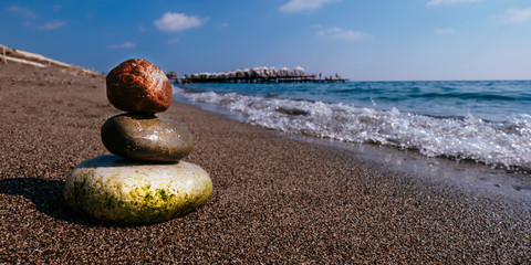 Photo sur Plexiglas Zen pierres a sable Stack of zen stones on beach near sea. Tower of spa rocks on sand at ocean. Balanced pebbles outdoors on sunny summer day. Oriental calm and harmony symbol. Wellness and tranquility concept