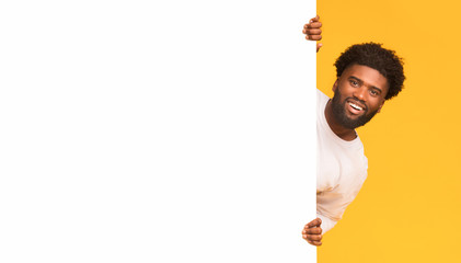 Smiling black guy looking over big blank white board