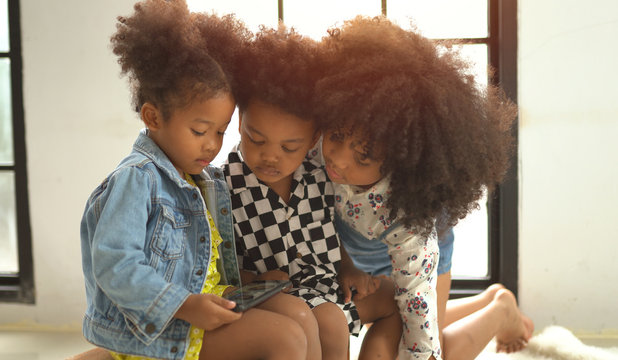 Afro children playing on smartphone