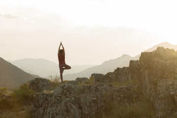 silhouette of woman doing yoga on top of mountain