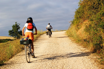 Couple of travelers on a touring bike traveling on a rural road in Spain in the direction of Santiago de Compostela.