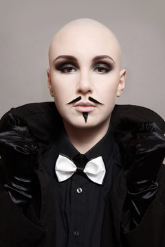 Vintage style portrait of skinhead woman with smoky eye makeup and fake mustache on her face