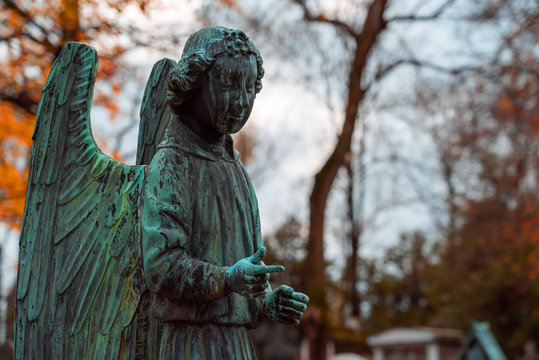 Old stone angel monument in the most famous cemetery of Paris Pere Lachaise, France. Tombs of various famous people. Golden autumn over eldest tombs.