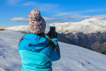 Young blonde girl with hat and blue jacket and phone in the snowy mountain. Technology concept