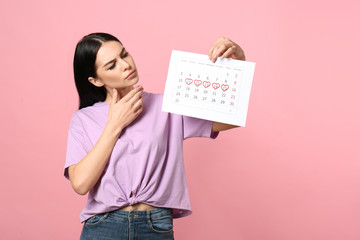 Fototapeta Pensive young woman holding calendar with marked menstrual cycle days on pink background obraz