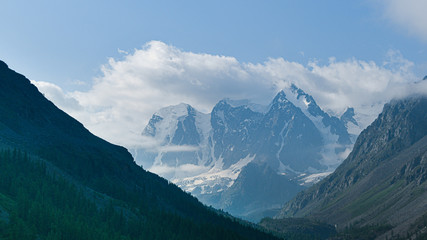 snowy mountain peaks on horizon of valley under clouds, travel to mountain area