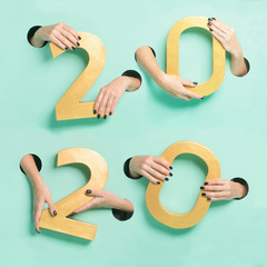 Female hands hold golden new year 2020 digits through a hole on neon mint background.