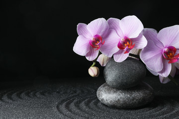 Photo sur Toile Zen pierres a sable Spa stones and orchid flowers on black sand with beautiful pattern, space for text. Zen concept