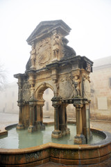 Renaissance fountain of Santa Maria and Seminary of San Felipe a foggy day in Baeza, Andalusia, Spain.