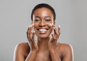 Fototapete - Portrait Of Happy Black Woman Applying Moisturizing Cream on Face