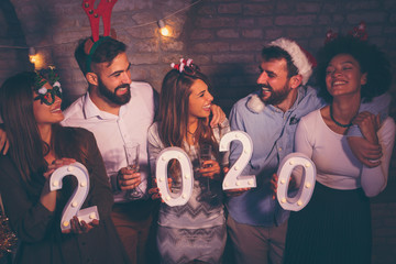 Group of friends holding illuminative numbers 2020 at New Years party