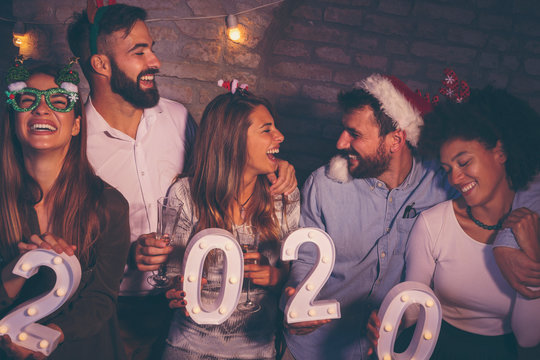 Group of people holding illuminative numbers 2020 at New Years party