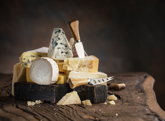Wall Mural - Assortment of different cheese types on wooden background.
