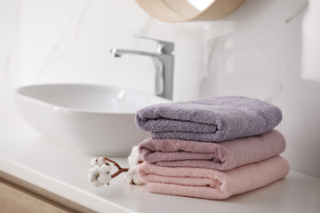 Stack of fresh towels and cotton flowers on countertop in bathroom