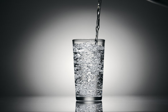 one glass of sparkling water on a dark background