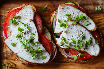 Sandwiches with turkey meat and fresh vegetables served with microgreens on a wooden plate. Top view, flat lay, macro food photography.