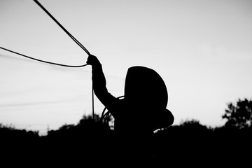 Young kid cowboy silhouette in black and white playing with rope to practice roping on ranch.