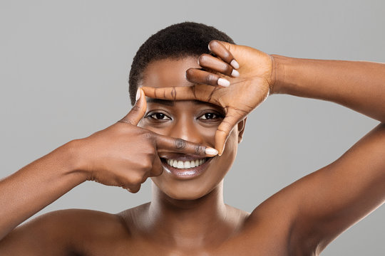 Attractive afro woman framing her beautiful eyes with fingers