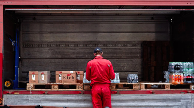 Minsk, Belarus - Nov 2018. Lorry with boxes of Coca-cola, water and juice. Delivery worker checks an order. food delivery to a restaurant, pub, cafe