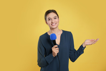 Young female journalist with microphone on yellow background
