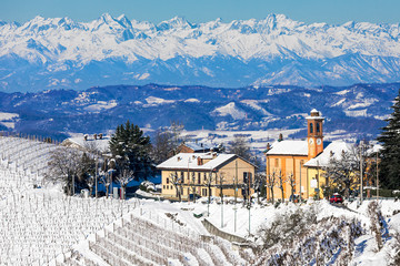 Rural house and parish church covered in snow in Italy.