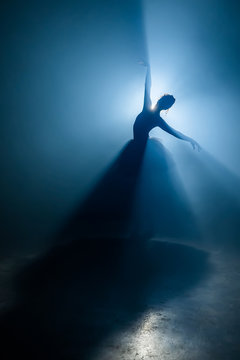 Solo performance by ballerina in tutu against backdrop of luminous spotlight
