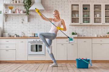 Happy woman dancing with mop and having fun while cleaning home