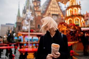 beautiful blonde with spit cake at the Christmas market in Wroclaw, Poland