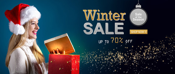 Winter sale message with young woman with Santa hat opening a gift box