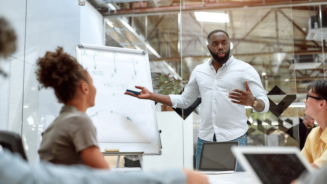 Good team leader. Young afro american businessman pointing at white blackboard and explaining new project to his colleagues while working together in the creative office